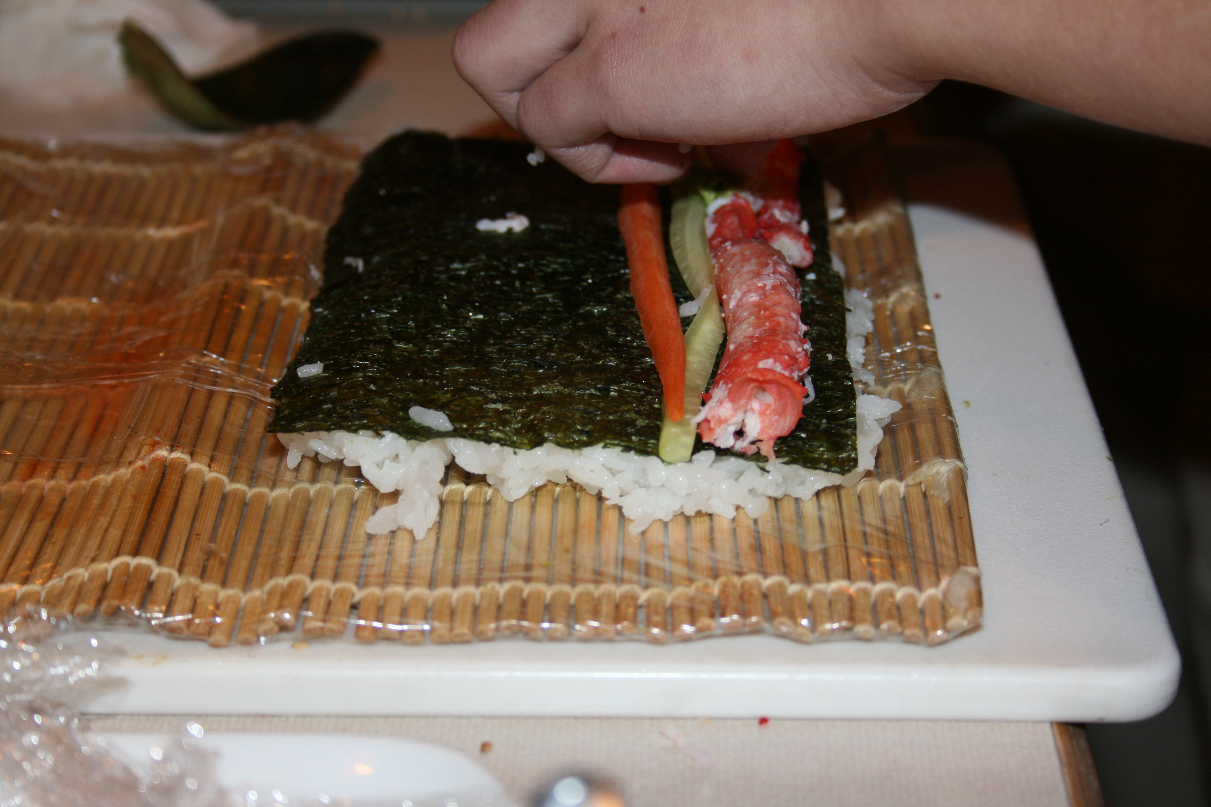 2. Flip sushi rice-topped nori sheet over and top with ...